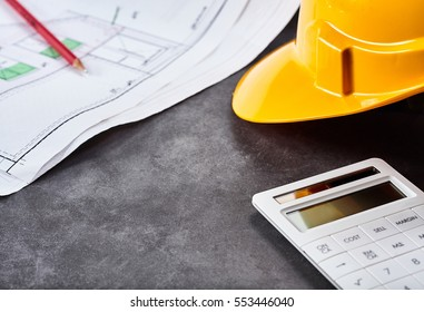 Construction work background with copy space surrounded by blueprint plans, pencil, yellow hardhat and calculator