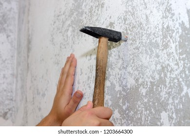 construction work, a hammer hammers a dowel into the wall, close-up