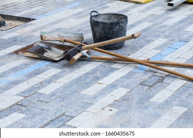 Construction work on pavement. Installation of concrete paver blocks on the sidewalk. A variety of tools left by the workers rests on the pavement already finished.