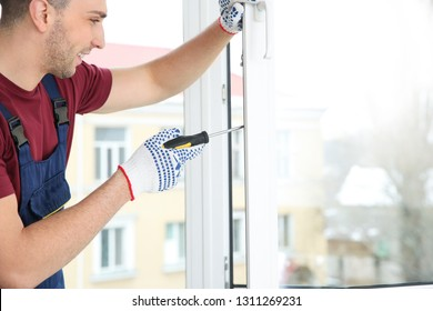Construction worker adjusting installed window with screwdriver indoors