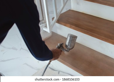 A construction worker applies varnish on the stairs. Using an airbrush for the application. Renovation or finishing works.