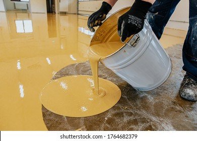 A construction worker apply epoxy resin in an industrial hall