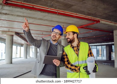 Construction worker and architect standing in building in construction process and discussing about project. Architect pointing at something.