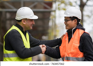 Construction worker and Asian architect shaking hands at construction site