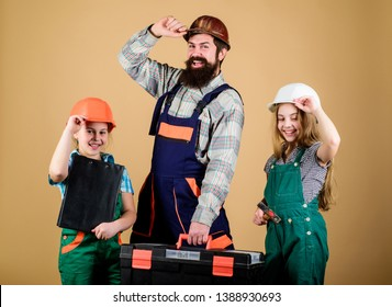 construction worker assistant. Builder or carpenter. Repairman in uniform. Engineer. Bearded man with little girls. Repair. Childrens creativity. Father and daughter in workshop. Confidence at safety.