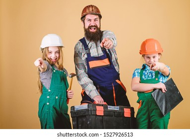 construction worker assistant. Builder or carpenter. Repairman in uniform. Foreman. Family teamwork. Repair. Father and daughter in workshop. Bearded man with little girls. Every detail is important.