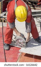 Construction worker bending over to use a rotary saw. Vertically framed photo.
