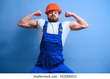 A construction worker in a blue uniform and an orange hard hat shows off big muscles with a serious face. A funny worker with strong hands and a grimace. Engineer brags about strength