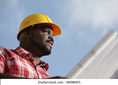 Construction worker with blueprints on a sky background