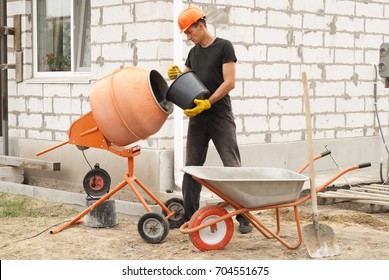 construction worker with a bucket in his hands loads a concrete mixer
