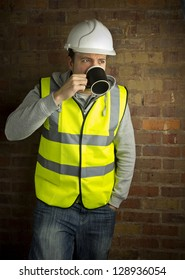 construction worker / builder on coffee break leaning against brick wall