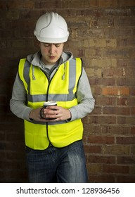 construction worker / builder on coffee break leaning against brick wall looking down