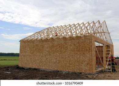 Construction worker building a detached garage with an open field in the background