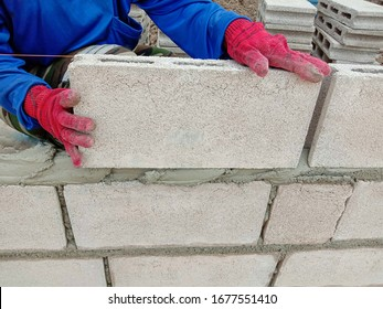 Construction worker is building wall by cement block closeup in construction site.