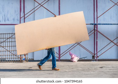 A construction worker carries a wooden board.
