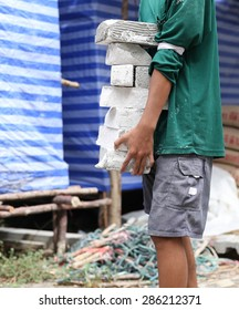 Construction worker carrying concrete block in building site