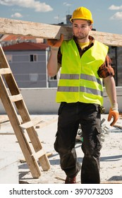 Construction worker carrying wooden beams, vertical image