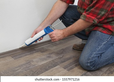 Construction worker caulking  batten of laminate floor using silicone glue in a cartridge, home renovation