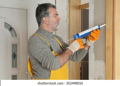 Construction worker caulking door  with silicone glue using cartridge