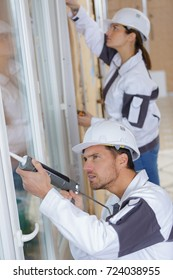construction worker caulking window with silicone