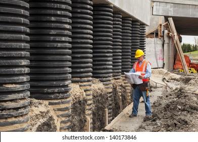 Construction worker checking blueprint at bridge construction site