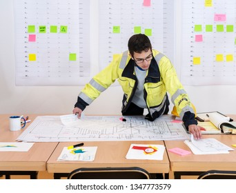 Construction worker checking design drawings in an office, wearing a safety jacket