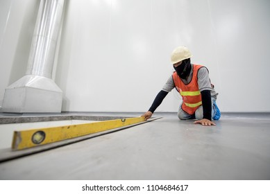 Construction worker checking level floor by spirit level