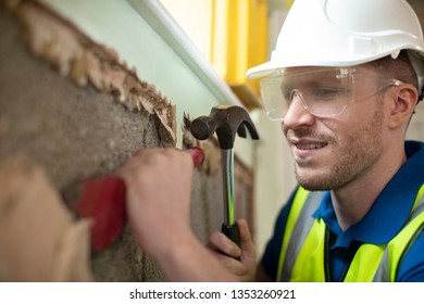 Construction Worker With Chisel Removing Plaster From Wall In Renovated House