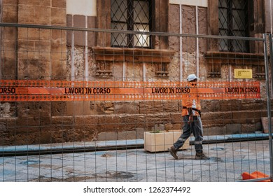 Construction worker in a city street working, lavori in corso sign, work in progress
