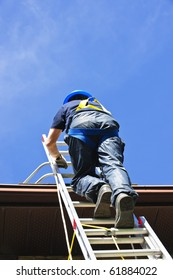 Construction worker climbing extension ladder to roof
