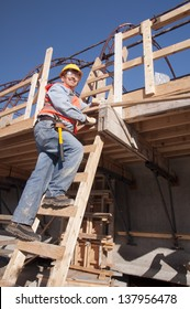 construction worker climbing ladder at construction site