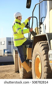 A Construction worker climbing a wheel loader