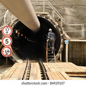 Construction worker climbs the stairs in the tunnel under construction. Technology adit tunnel complex combined rail and road to Krasnaya Polyana.