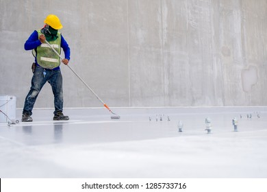 Construction worker coating floor by epoxy