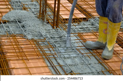 Construction worker compacting liquid cement in reinforcement form work during concreting floors pouring works