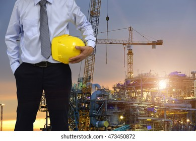 Construction worker concept . engineer  holding helmet and construction plant sunset background