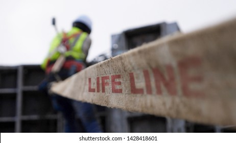 Construction worker connected with a safety harness to a life line system for builders