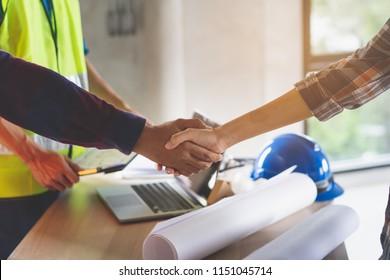 Bauarbeiter und Bauunternehmer. Der Kunde schüttelt mit dem Teambauer in der Renovierungsstätte die Hände.