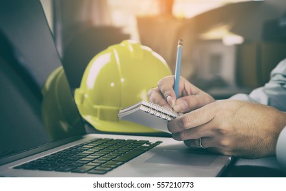 Construction worker contractor in Construction industry is taking note on computer. Modern Engineer  is working in office.