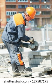 construction worker at curb stone cutting work by cut-off saw with diamond wheel grinding machine