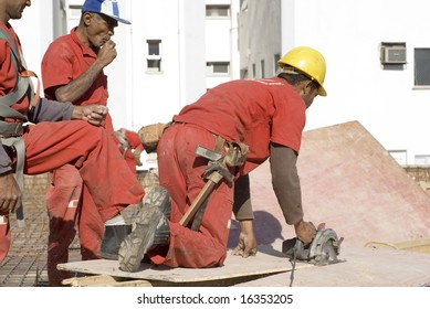 Construction worker cuts board with skill saw. He is wearing a tool belt and two other workers are watching him. Horizontally framed photo.