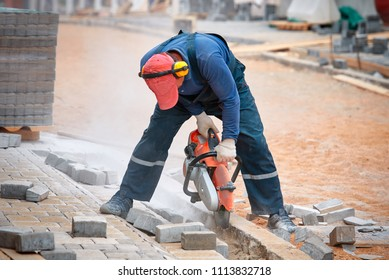 Construction worker cuts walkway curb with circular saw. Man Protect Hearing From Noise Hazards on the Job. Tiles piled in pallets on background. sawn paving slab next to the worker