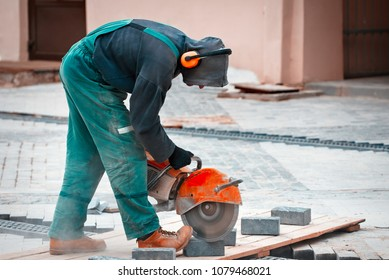Construction worker cuts walkway slab with circular saw. Man Protect  Hearing From Noise Hazards on the Job
