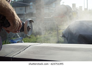 Construction worker cutting concrete plate for fence fundation using a cut-off saw.