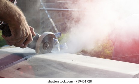 Construction worker cutting concrete plate for fence foundation using a cut-off saw.