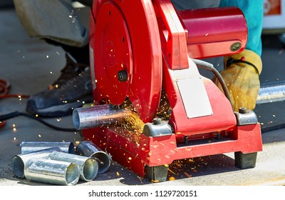 A construction worker cutting a galvanized steel pipe with a chop saw chop saw