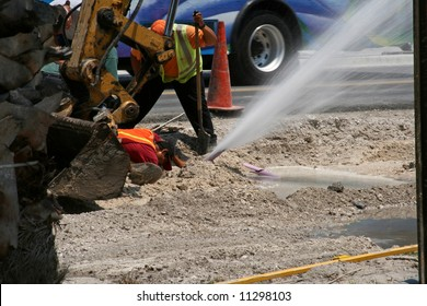construction worker digging up the road strikes a water pipe