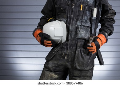 Construction worker in dirty overalls in Finland. The laborer have orange gloves, white helmet and hammer. Background out of focus and illuminated with flash. Image includes a effect.