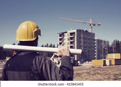 Construction worker in dirty overalls and a white helmet in Finland. In his hand he has drawings. In the background is out of focus in the construction site. Image includes a vintage effect.