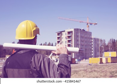 Construction worker in dirty overalls and a yellow helmet in Finland. In his hand he has drawings. In the background is out of focus in the construction site. Image includes a vintage effect.